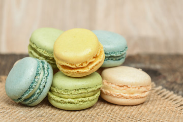 Macarons piled on burlap napkin in rustic setting