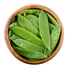 Snow peas in a wooden bowl on white background. Pisum sativum saccharatum, a green legume and variety of pea, eaten whole in its pod while still unripe. Isolated macro food photo close up from above.