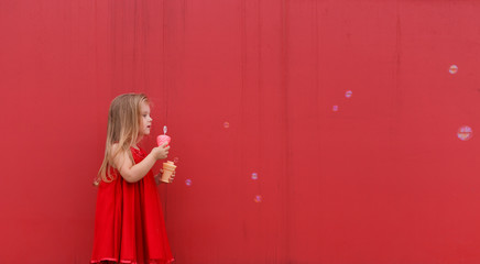 little girl in red dress blowing soap bubbles on the  background