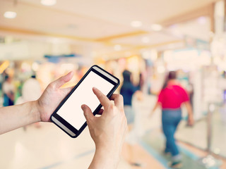 Hand woman holding and using phone with blurred background in shopping mall.