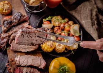 Piece grilled steak on a fork.