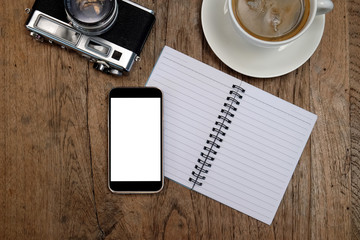 Smart phone on notebook with camera classic and coffee on wooden