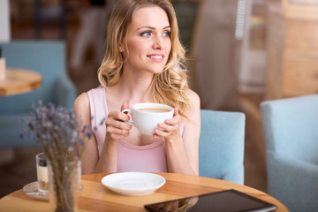 Cute young woman drinking coffee