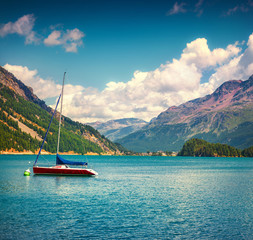Summer sunny scene on the Silsersee lake with small yacht.
