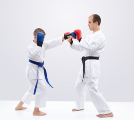 Boy karateka is  training strikes on the trainer overlays