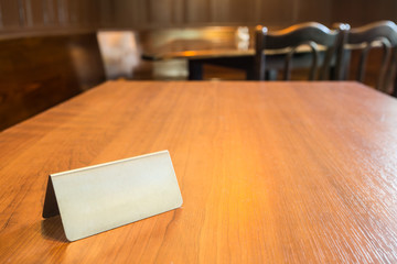 restaurant interior with a wooden table and a blank steel plate on it