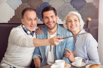 Cheerful couple and their grandson making selfies