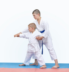 Brother with a blue belt teaches the brother with a white belt to beat the punch arm