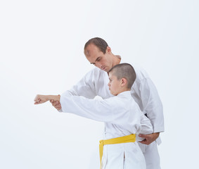 On a white background coach teaches the athlete to beat a punch arm
