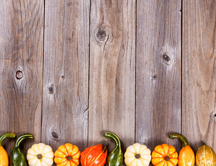 Bottom border of autumn gourd decorations on rustic wooden board