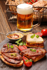 Sandwich with fried bacon and beer on wooden background