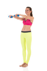 Smiling brunette woman in sports neon yellow leggings and pink bra doing complex exercises for muscles of hands using blue dumbbells