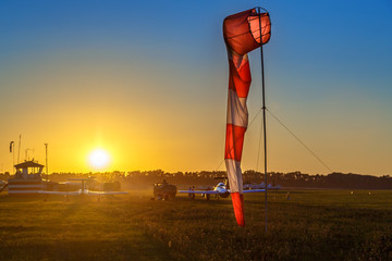 Airfield sign of the direction and force of the wind against sunset sky. Airdrome scene.