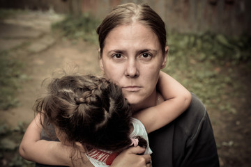 A woman holds a child, trying to calm him down. The child is three years.