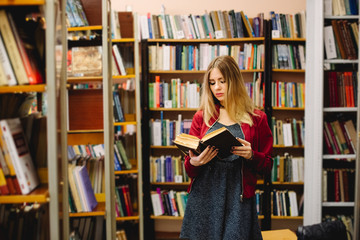 Female student reading a book between bookshelves in university library