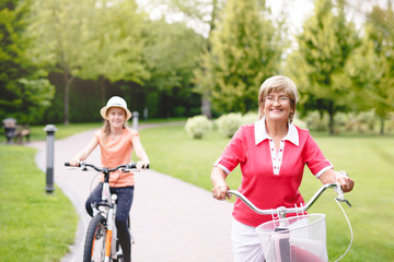 Happy active senior woman riding bike with her grandaughter in park at summer