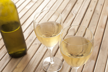 Glasses of white wine with a bottle