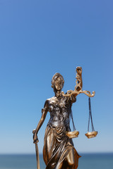 Back side view of Themis - Lady of Justice on blue sky background