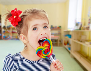 Girl licks candy on a stick