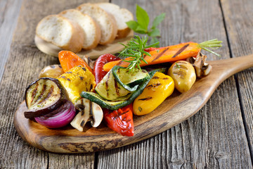 Vegan grillen: Gemischtes Gemüse vom Grill mit Kräutern, Gewürzen und Olivenöl, dazu frisches Ciabattabrot - Mixed grilled vegetables on a wooden cutting board served with Italian ciabatta bread