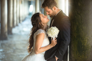 Passionate stare and kiss romantic attractive lovers bride and handsome groom couple