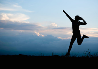 Silhouette of Happy woman jumping in green field against blue sk