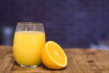 Glass of orange juice with half an orange