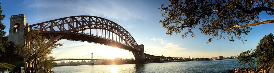 The Hell Gate Bridge over the river with sunset sky in panorama shot, Astoria park, Astoria, Queens, New York