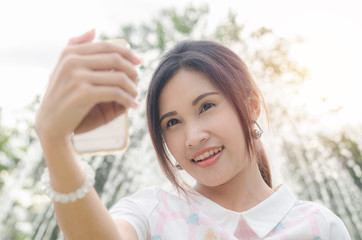 Beautiful asian girl taking her photo by smart phone outdoor