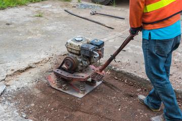 Worker reversible plate compactor on a roadwork site. Excavator in background.Repair cracked Sidewalk