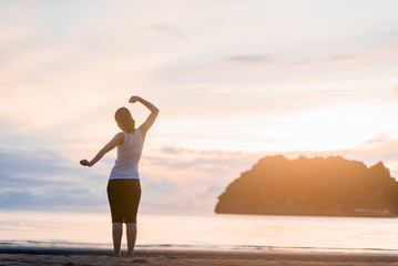Relaxed woman breathing fresh air at on the beach sunrise.