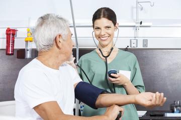Happy Nurse Examining Blood Pressure Of Man In Rehab Center