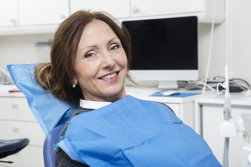 Smiling Patient Sitting At Dentist's Clinic