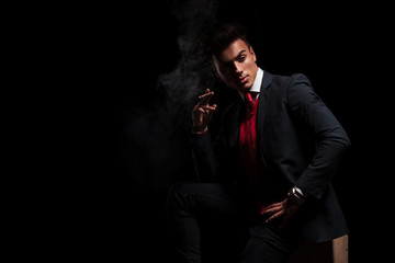side view of an elegant young businessman smoking a cigarette