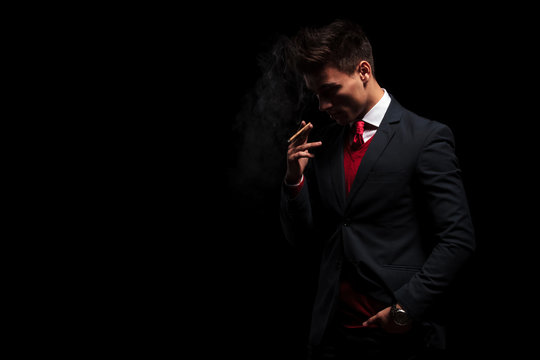 young business man is thinking while smoking his cigarette