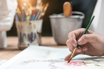 Artist is painting flower by watercolor on paper