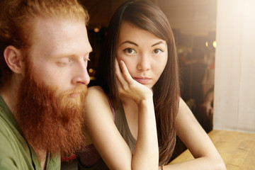 Interracial couple. Indoor portrait of freckled Caucasian man looking angry and disappointed with his Asian girlfriend who is having surprised and sad face expression, resting her cheek on hand