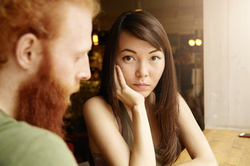 Multiethnic couple. Selective focus. Asian girl with worried look, resting elbow on table, sitting in front of her hipster boyfriend. Woman and man having serious talk about their relationships