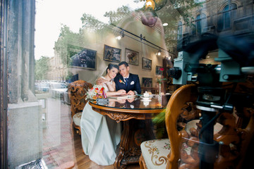 Lovely wedding couple throgh cafe's window