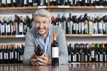 Happy Man Holding Wine Bottle While Leaning On Table
