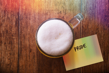 Glass of Beer on the Wooden Table at Bar with Rainbow light , Paper Note and Word : Pride, Gay Concept