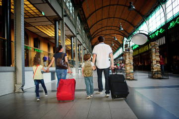 Father, mother and two children pass the waiting room at the station.