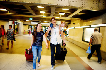 Young pair with a daughter hasten at train station.