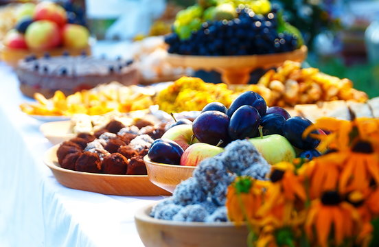 Beautiful wedding feast in nature, abundance of meals on a table.
