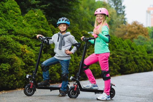 Happy kids standing on electric scooter outdoor