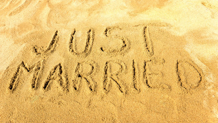 Words just married handwritten on the sandy beach