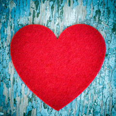 Red felt heart on an old painted wooden background