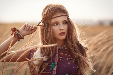 Fashion portrait of beautiful hippie woman at the sunset summer