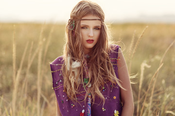 Fashion portrait of beautiful boho woman in the sunset field loo