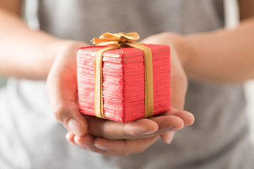 Woman holding red gift box by hand